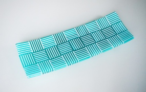 Strip constructed platter of aqua and white strips carefully aligned in an alternating grid of squares